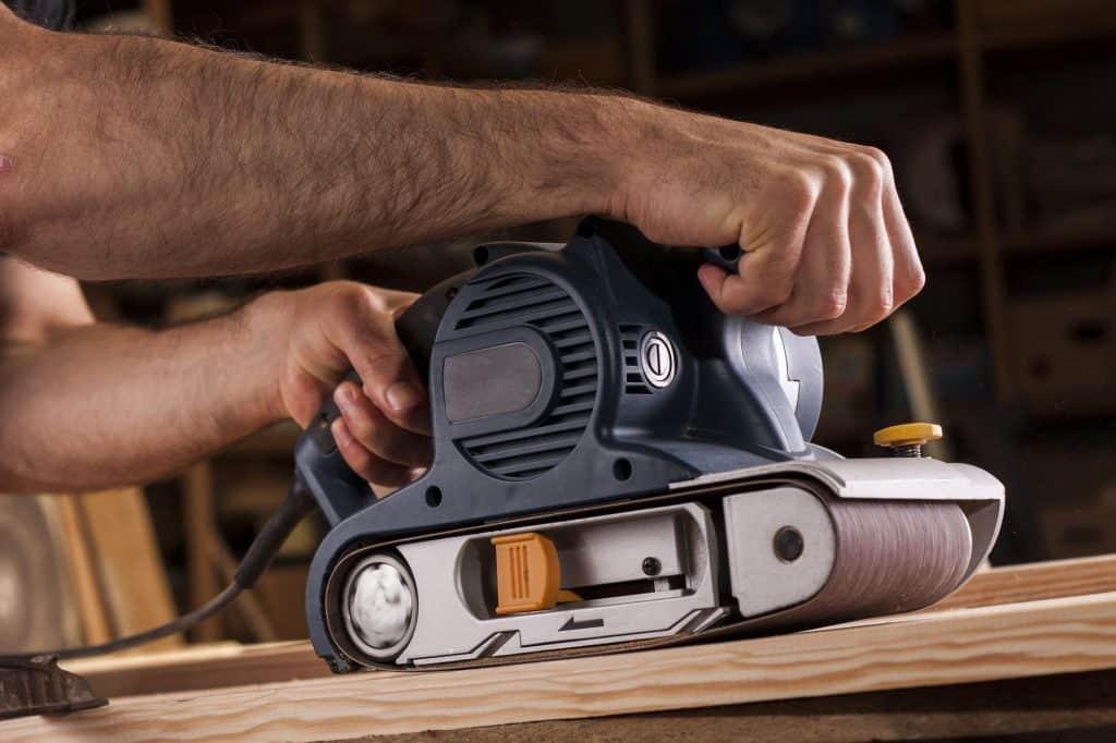 sanding wood with a belt sander