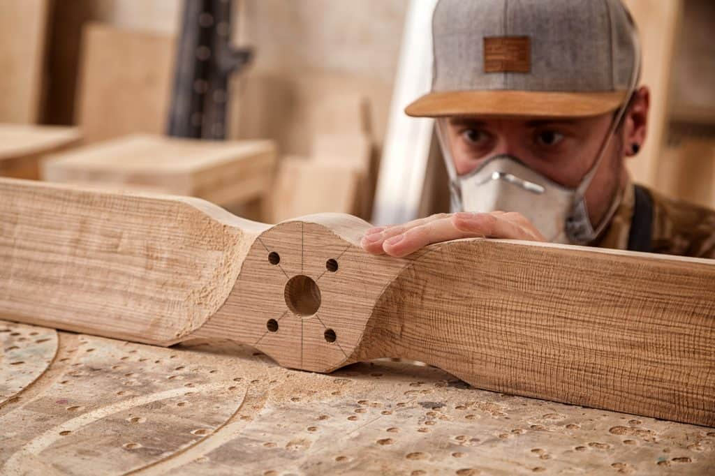 man with curved wood sanded with a spindle sander