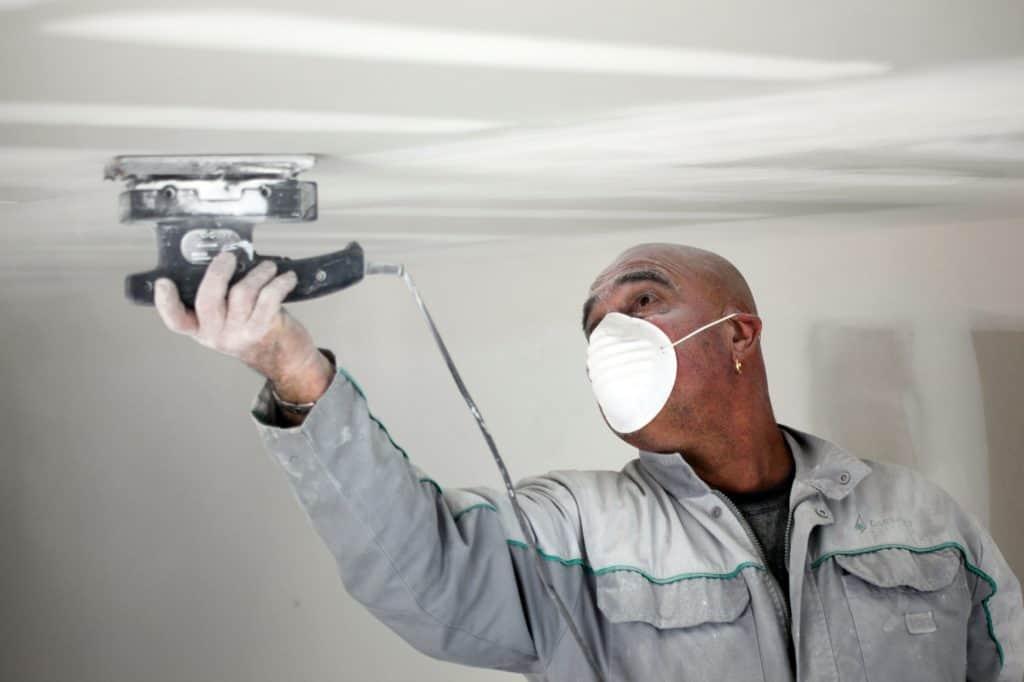 man sanding drywall