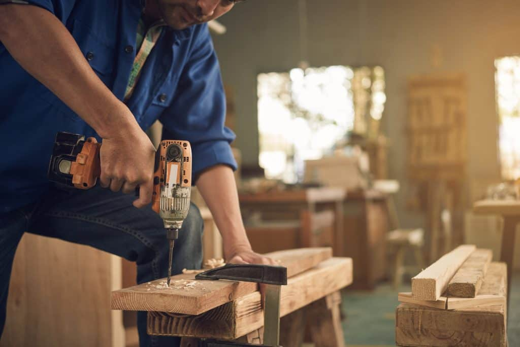 man drilling plank