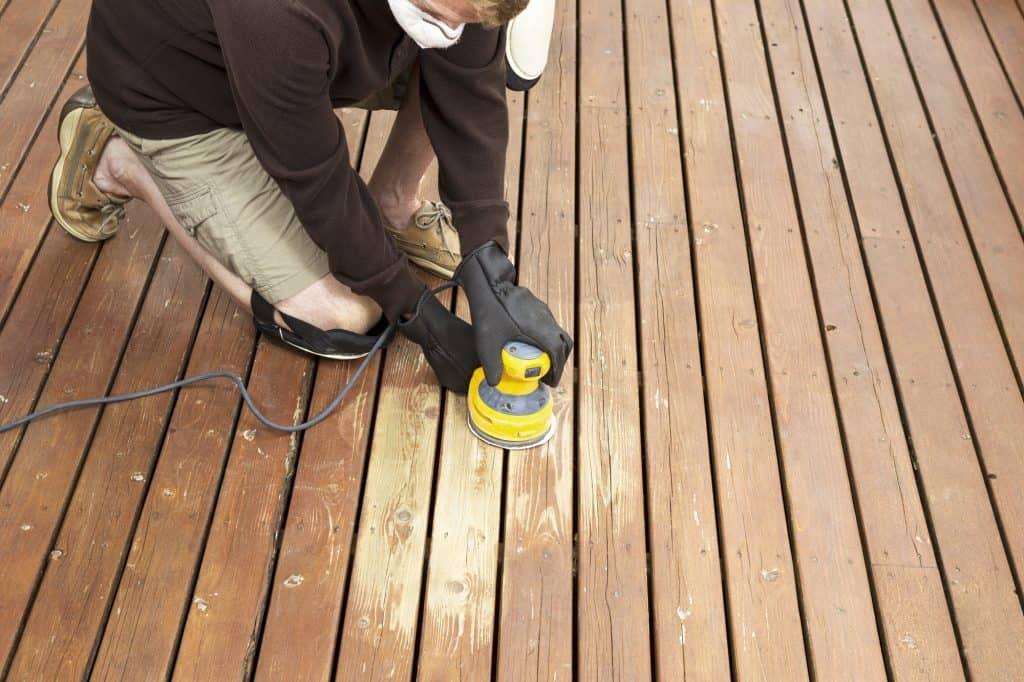 man sanding wooden deck