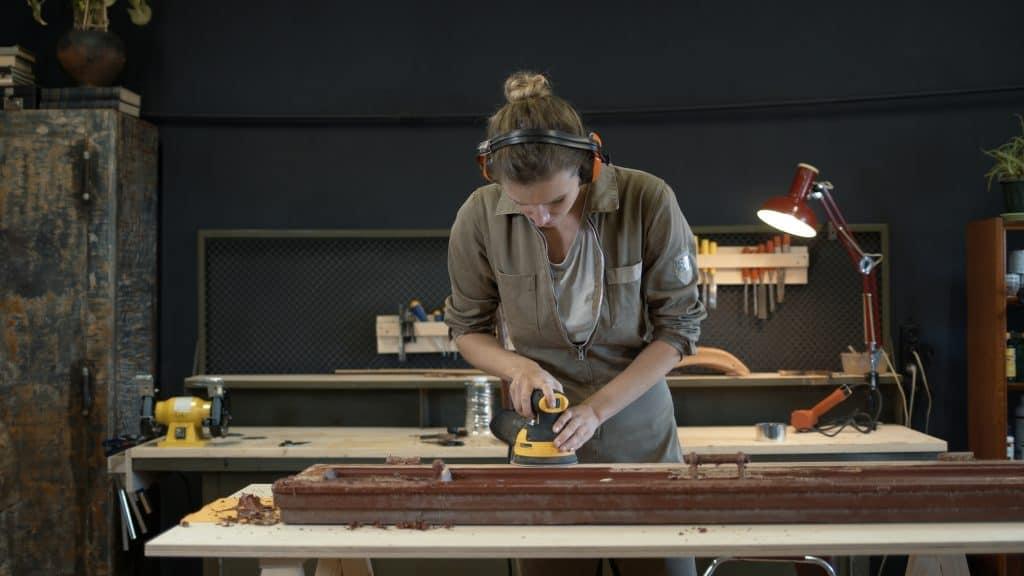woman detail sanding a wood frame