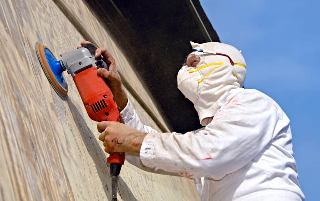 man wearing a dust mask and sanding a wall