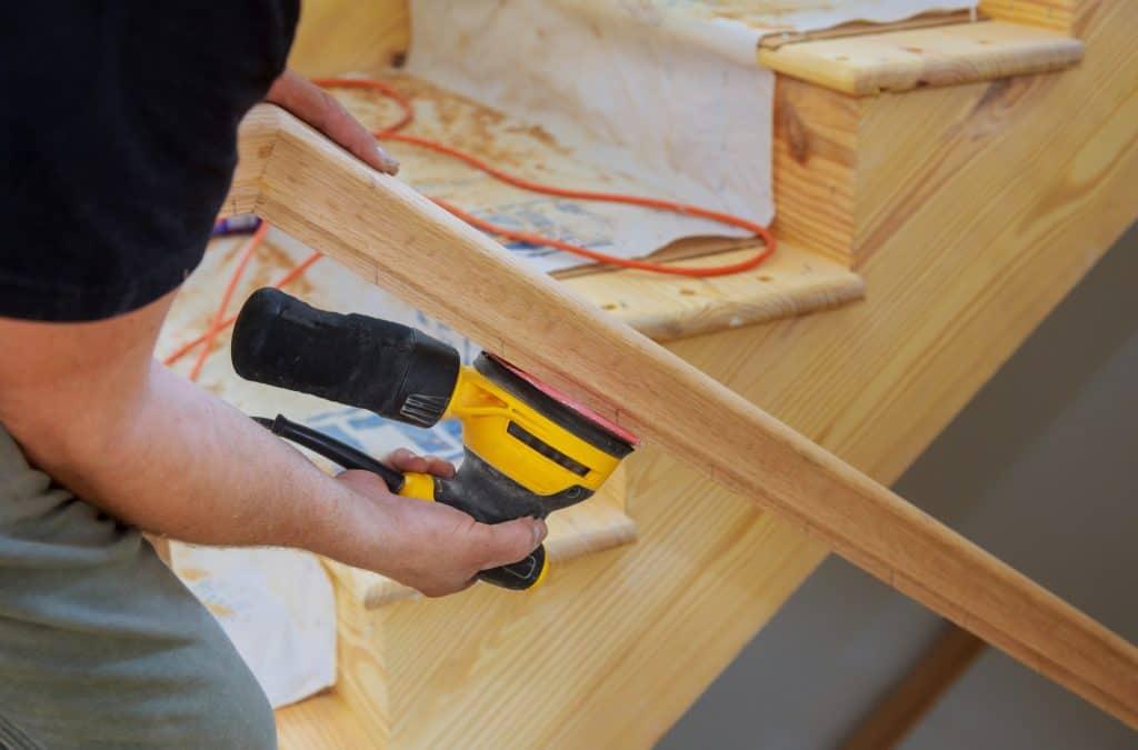 man sanding wooden stairwell