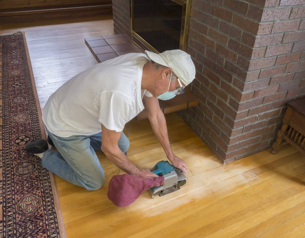man sanding between polyurethane coats