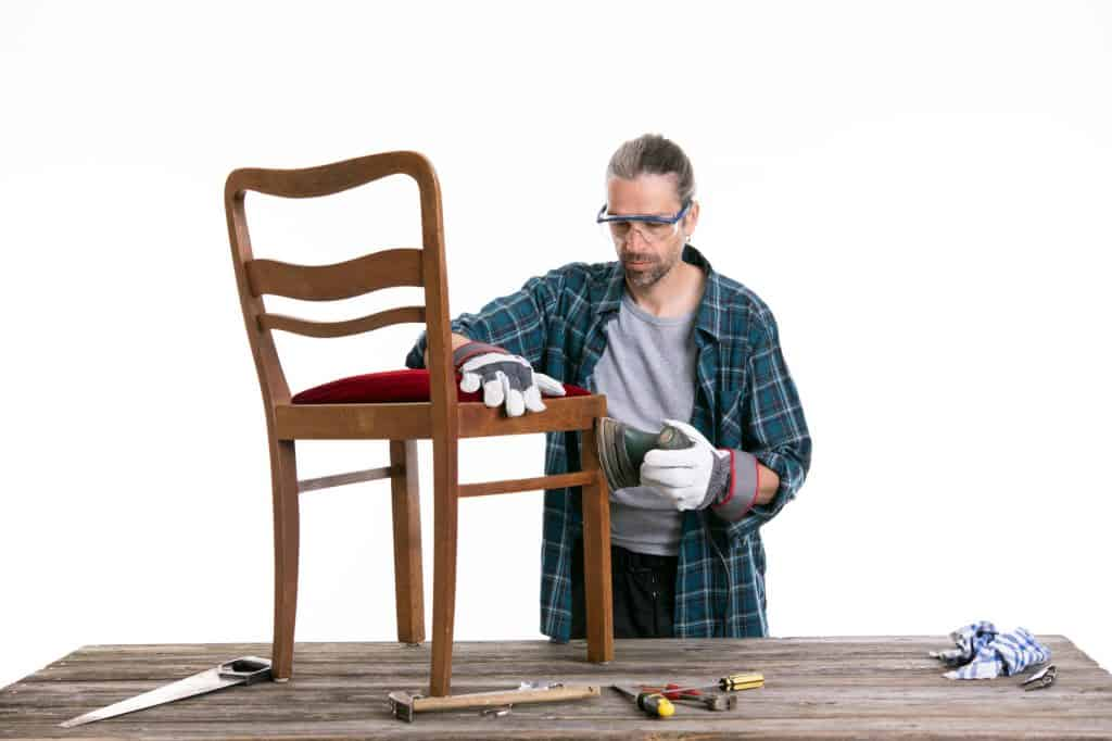 sanding a chair with a mouse sander