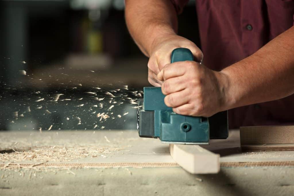 a carpenter using a planer