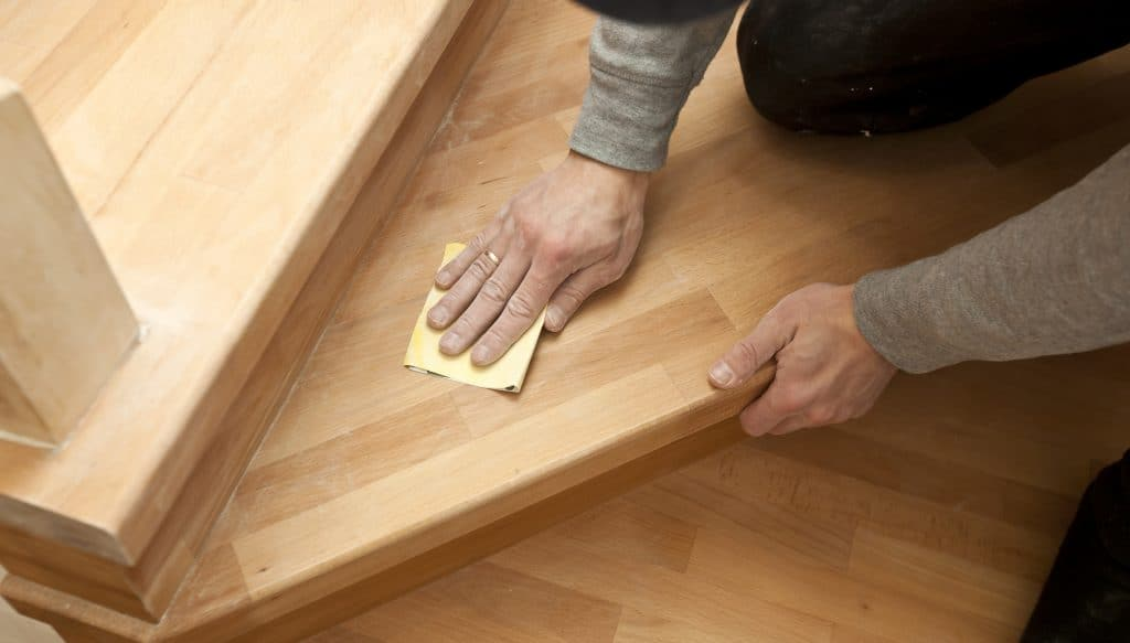 a man using a sandpaper to remove polyurethane from off wood