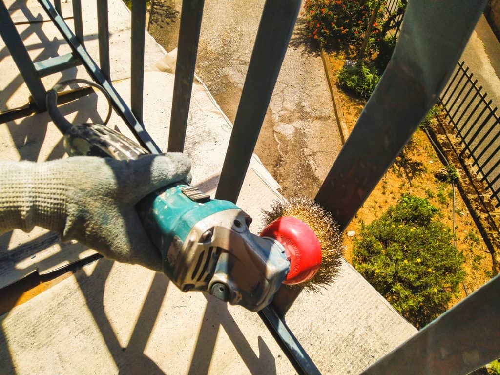 a man using a sander to clean the railings