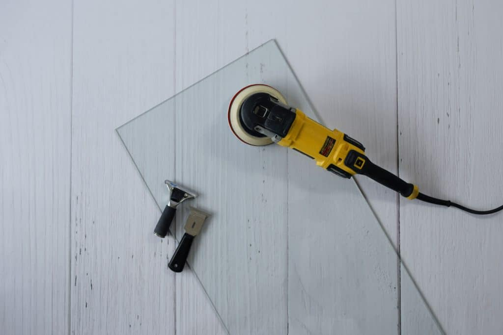 a piece of glass and a sander on the floor