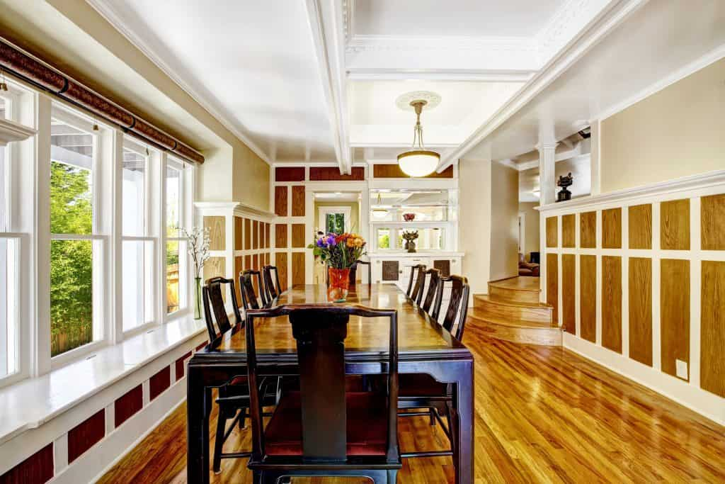 a dining room with wood trims, wooden floors and cabinets