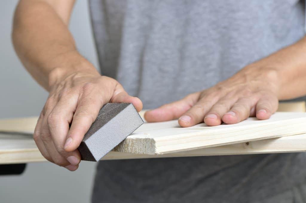 man sanding a wooden board with a sanding block