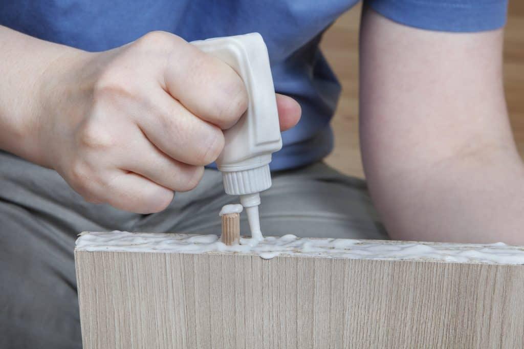 man putting glue on a piece of wood
