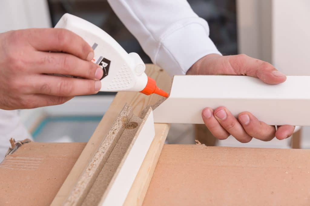 carpenter applying wood glue on a wooden door frame