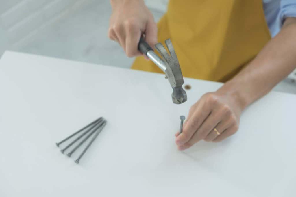 man hammering the nail